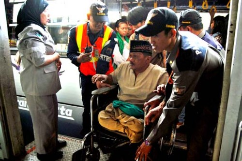 Transjakarta officers help a wheel chair-bound man debark from a crowded bus at the Matraman busway stop in Central Jakarta
