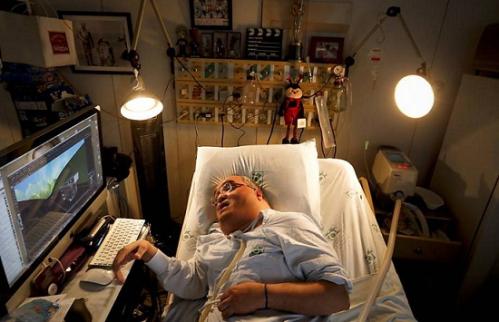 Paulo Henrique Machado deitado na cama do hospital, ao lado do computador de onde criou toda a sua animação