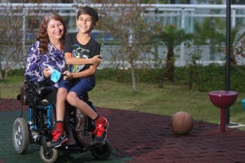 Margarida e o filho Raphael, que sempre adorou a carona na cadeira de rodas