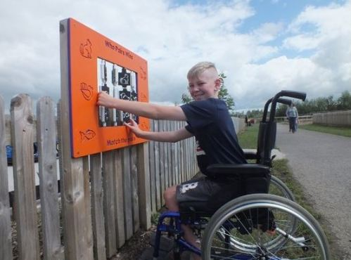 Jack Long, a children on a wheelchair, using activity boards