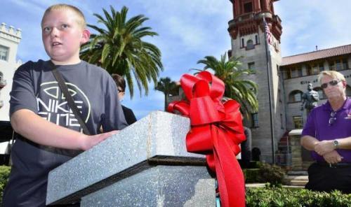 Blind student Rich Beardsley reads a Braille inscription on a marker describing the statue of Don Pedro Menendez de Aviles