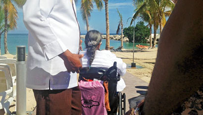 A traveler in a wheelchair is escorted by a tour guide at the Riu Palace Jamaica in Montego Bay
