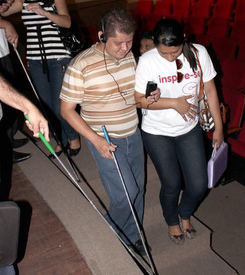 Participantes do projeto descem a escada sem corrimão que dá acesso ao palco do Teatro 04 de Setembro com ajuda de uma outra pessoa