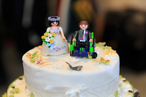 The wedding cake ornament, with characterized dolls, showed the groom Tim in his wheelchair