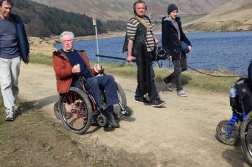 BBC Countryfile presenter John Craven tries out a 'mountain trike' off-road wheelchair while filming with Huddersfield based group Community Experience