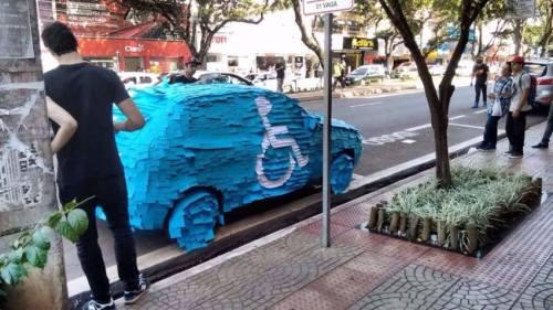 O motorista do carro vermelho do infrator que estacionou numa vaga de estacionamento para deficientes foi humilhado e multado