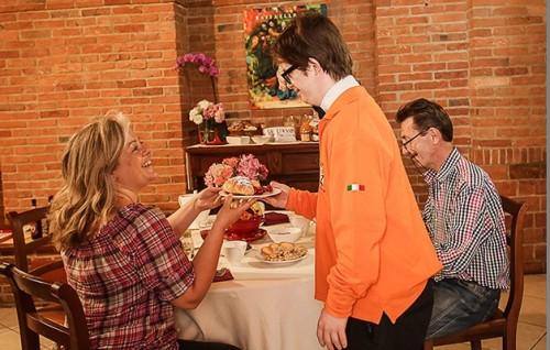Jovem com síndrome de down serve casal sentado na mesa