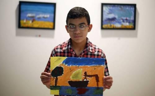 O garoto jordaniano cego Ahmad Qouqaz possui com o trabalho que fez e é parte de exposição no país
