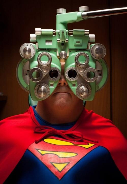 Síndrome de Down Michael de Super Homem com um aparelho oftalmológico em frente do rosto