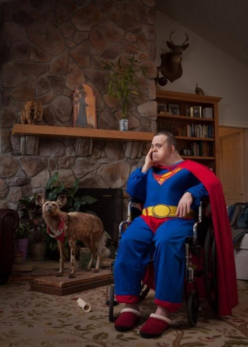 Síndrome de Down Michael de Super Homem sentado em uma cadeira de rodas