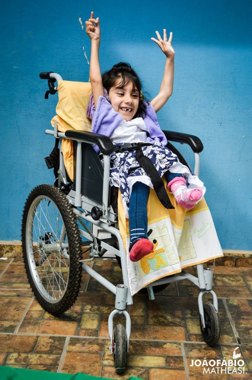 Esta foto é a Pri em sua cadeira de rodas, Pri está linda e sorridente.