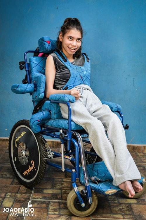 Nara em sua cadeira de rodas, sorrindo e feliz