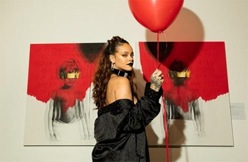 Rihanna posa na frente da capa e da contracapa de seu novo álbum, que tem as informações em braile. Ela usa roupas pretas e segura uma bexiga vermelha.