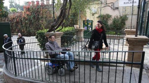 Antonio Hierro sube por una rampa con su silla de ruedas, en un recorrido por los Jardines de Murillo, en compañía de Sara López