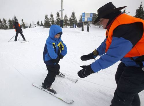 Reece Drapeau, visually impaired, gets some instruction from Steve Cowboy Piersch, during a ski lesson at Sundown Mountain Resort, in Dubuque