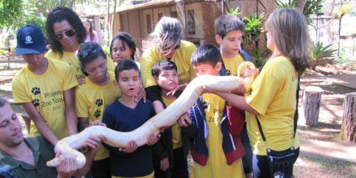 Crianças cegas tem a experiência de tocar em uma cobra no Zoológico de Brasília