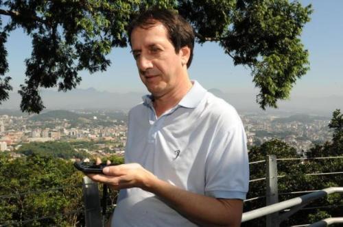 O professor Osmar Pavesi, que é deficiente visual, usa um telefone celular para ouvir a audiodescrição