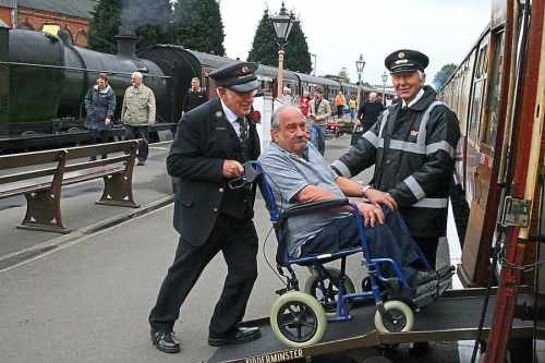 Severn Valley Railway staff help a disabled passenger onto one of their trains