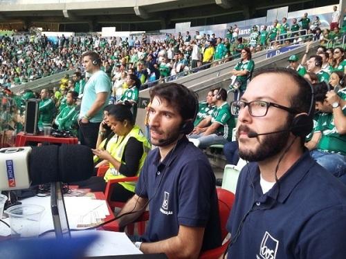 Audiodescritores sentados em uma mesa usando fones de ouvido e com microfones, ao fundo os torcedores com deficiência visual
