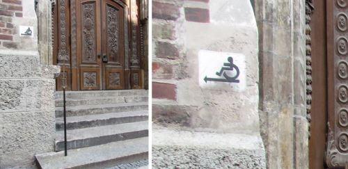 Frauenkirche em Munique, Alemanha. Entrada principal com escadas possui sinalização indicando o local de acesso sem barreiras