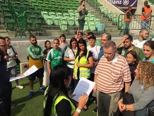 Grupo de cegos fazendo o reconhecimento tátil do campo. Bruno e Rosa a frente com papéis nas mãos.