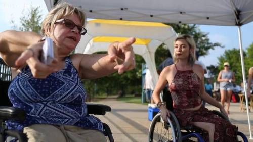 Kristine Newbold shows a wheelchair rodeo participant how to avoid barriers while riding a wheelchair at Woodruff Park in Columbus.