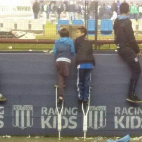 Santiago Fretes, de 10 anos, emprestou uma de suas muletas para o amigo ver jogo do Racing