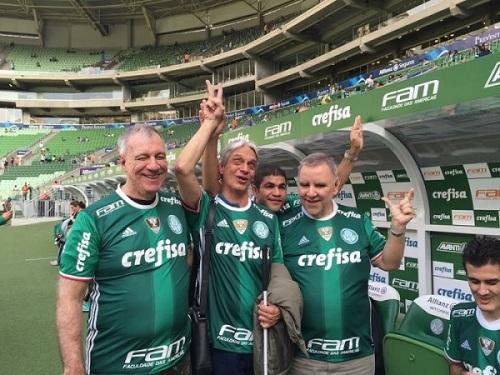 Torcedores cegos no gramado. Eles vestem a camisa do Palmeiras, estão abraçados e comemoram cantando o hino do time