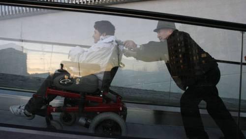 Un hombre empuja cuesta arriba a una persona en silla de ruedas por la rampa mecánica que une las calles Abejeras y Río Ega.