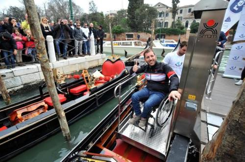 a-man-sitting-on-a-wheelchair-is-boarded-on-a-gondola-in-venice-italy