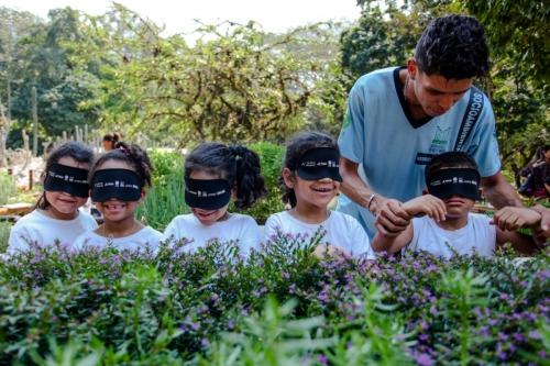 los-ninos-caminan-por-el-jardin-sensorial-con-los-ojos-vendados-guiado-por-una-persona-ciega-simplemente-a-tocar-y-oler-las-plantas